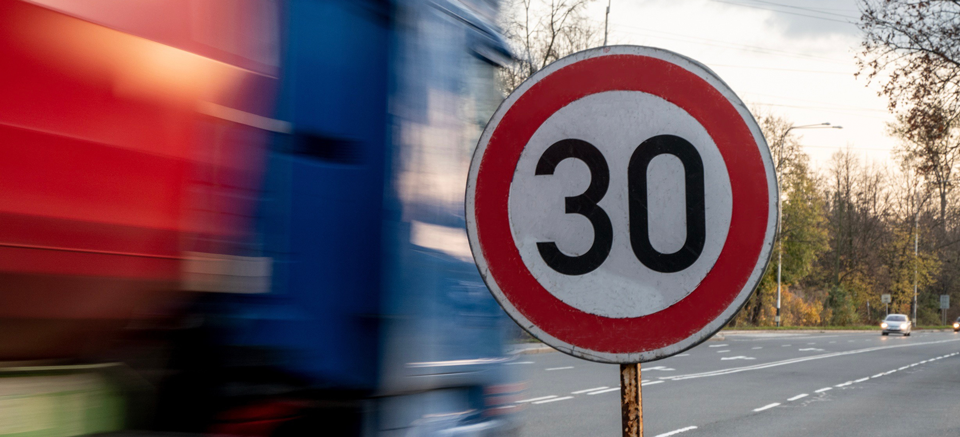 A fast driving blue speeding truck with motion blur effect near the traffic sign limiting the maximum speed to 30 kph